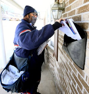 U.S. Postal Service carrier Michelle Rehmeyer delivers mail at a residence on East Center Street during her route in Glen Rock Wednesday, Feb. 24, 2021. She's worked for the Postal Service for 16 years. Bill Kalina photo