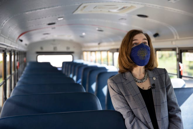 Gov. Kate Brown visits with school bus driver Alan Booth Feb. 24 at Kalapuya Elementary School in West Salem, as schools prepare to reopen.