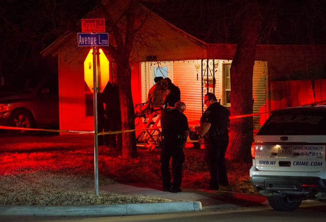 Wichita Falls police investigate the scene of a murder Tuesdday night at a house on Grant Street.