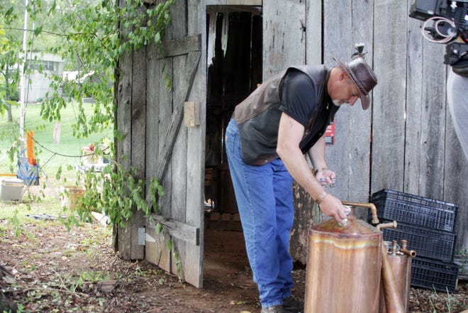 """""""Big Steve"""" Watson of Duncan Falls looks for still parts during the filming of Moonshiners: Master Distiller. Watson's episode aired on the Discovery Channel on February 9."""