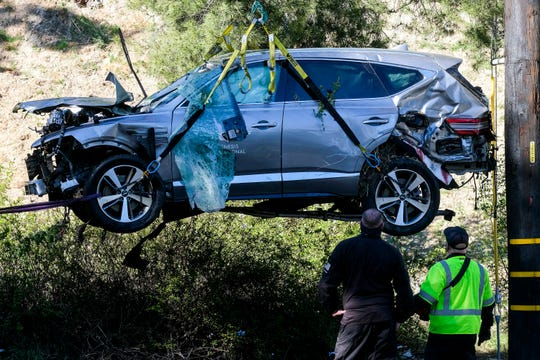 Workers watch as a crane is used to lift a vehicle after an accident involving golfer Tiger Woods, Tuesday, February 23, 2021, in the Rancho Palos Verdes section of Los Angeles.