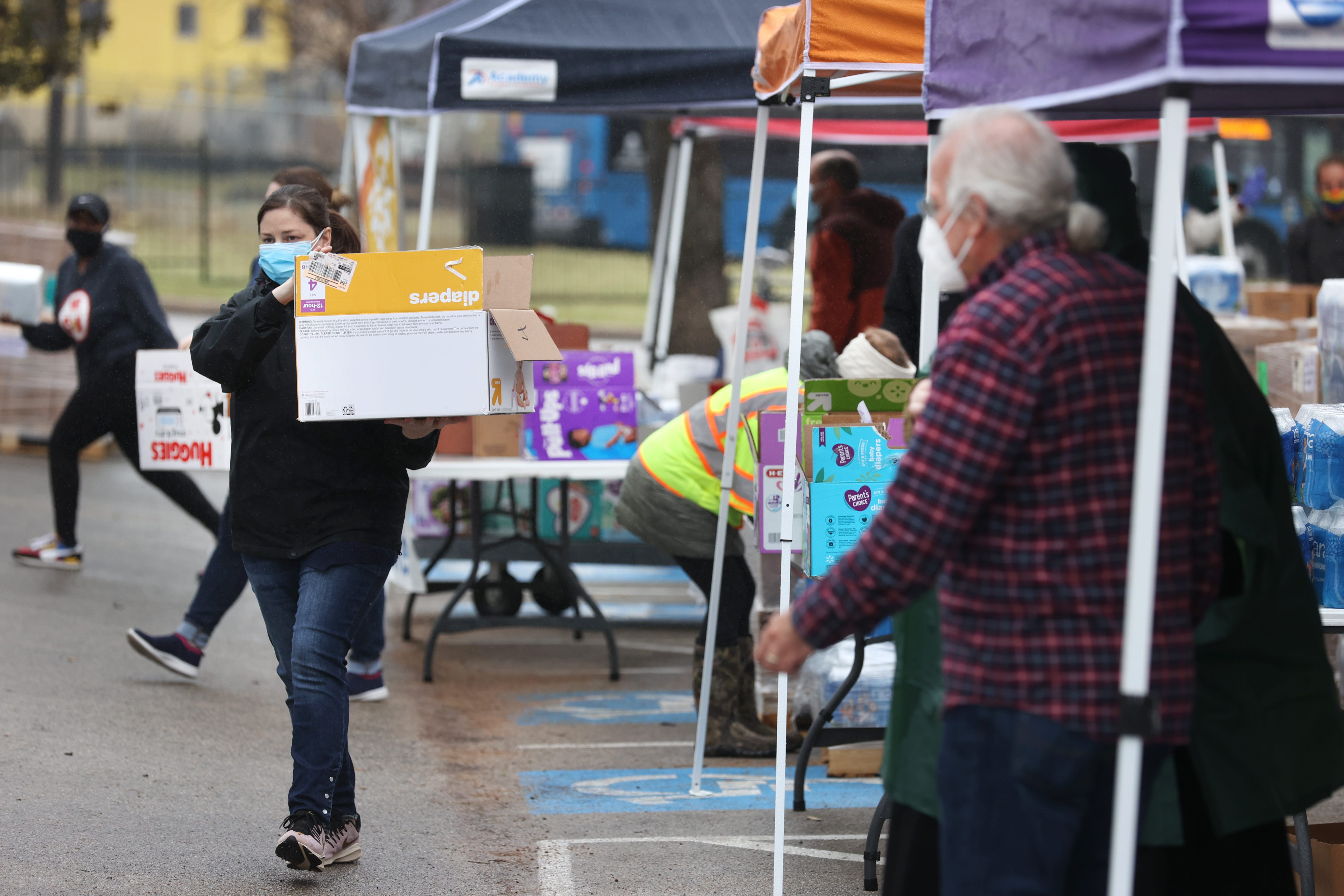 Workers help to dispense food, water and hygiene products to people in need at the Millennium Entertainment Center food distribution site in East Austin on Thursday, Feb. 25, 2021.