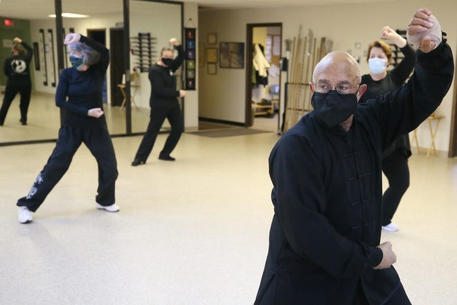 Gary Harris, right, owner of the Center for Body-Mind Harmony in Cuyahoga Falls, leads a class in tai chi Tuesday.