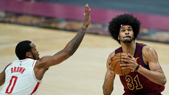 Cleveland Cavaliers' Jarrett Allen (31) drives to the basket under pressure from Houston Rockets' Sterling Brown (0) in the first half of an NBA basketball game, Wednesday, Feb. 24, 2021, in Cleveland. (AP Photo/Tony Dejak)