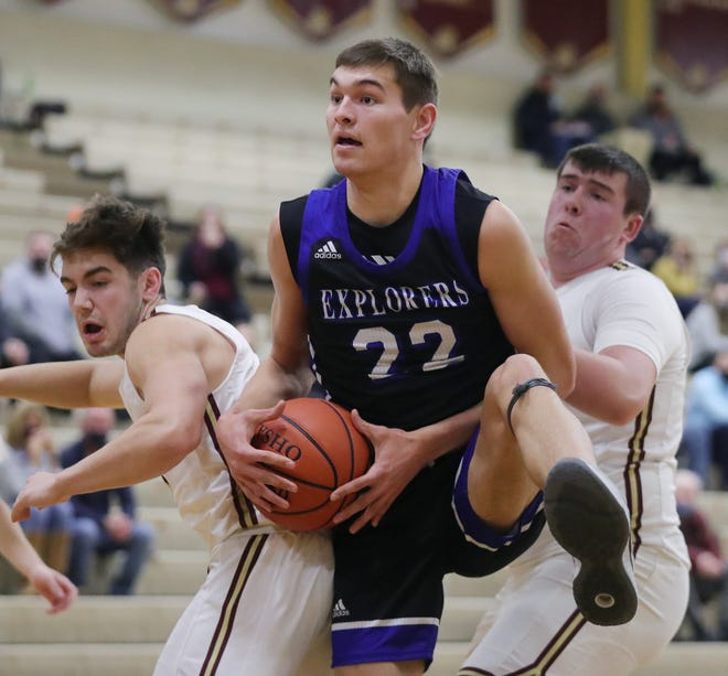 Hudson's David Gentry, center, brings down a rebound between two Stow defenders in the first half of the Explorers' 40-32 win in a Division I sectional semifinal Wednesday night at Stow. [Jeff Lange/Beacon Journal]