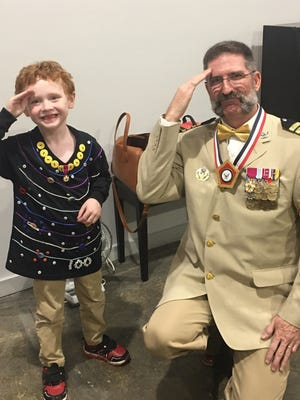 """Aaron Turner, age 6, created his own Colonel Mustard costume after being inspired by the Brownwood Lyric Theater's production of """"Clue."""" He is shown with Joe Dennis, who was cast as Colonel Mustard in the Lyric show. Dennis gave Aaron a medal for him to wear on his costume. Aaron duplicated costumes for more than a dozen of the """"Clue"""" characters."""