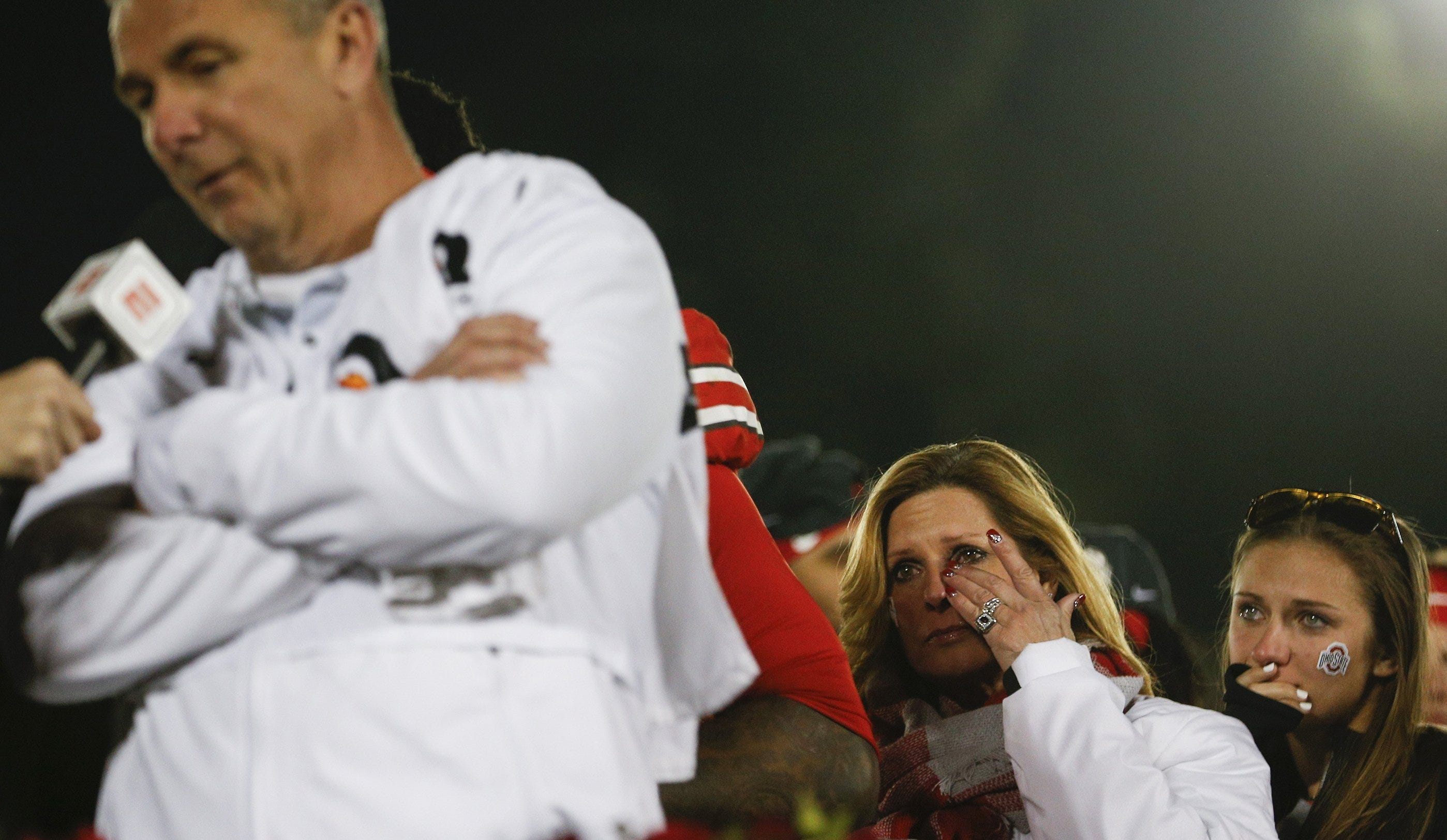 Shelley Meyer, second from right, and Gigi Meyer, right, wipe away tears as Ohio State Buckeyes head coach Urban Meyer speaks on Jan. 1, 2019 at the Rose Bowl in Pasadena, Calif.