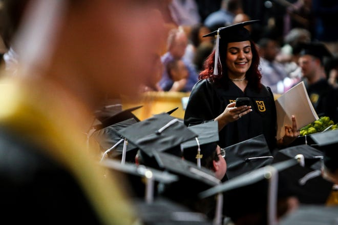 A graduate looks at her phone during the University of Missouri College of Arts & Sciences graduation May 12, 2018, at Mizzou Arena.