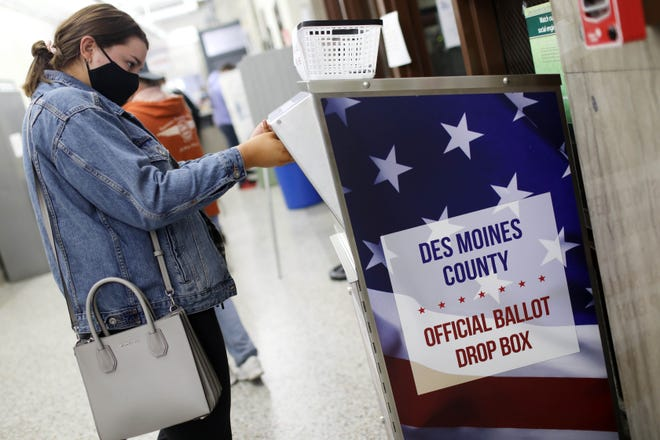 Alexa Jaeger places her ballot into a drop box as Iowa voters visit the county auditor's offices to vote early in person Oct. 30, 2020, at the Des Moines County Courthouse in Burlington.