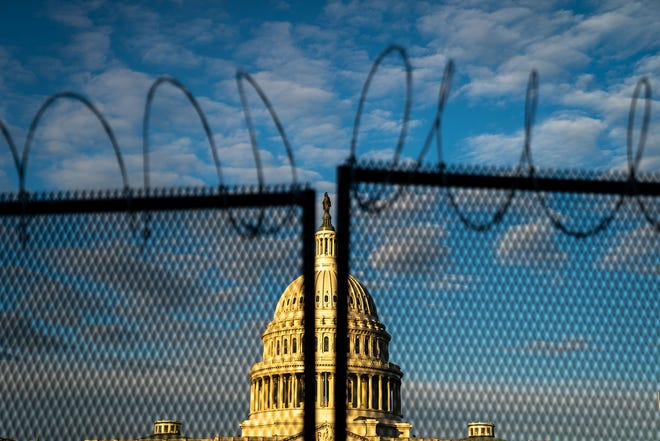 Barbed wire, is seen atop security fencing, with the dome of the U.S. Capitol Building on Saturday, Jan. 16, 2021, in Washington, D.C.
