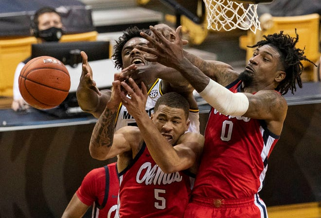 Mississippi's Romello White, right, and KJ Buffen, center, and Missouri's Kobe Brown, left, vie for a rebound during the second half of Tuesday's game in Columbia, Mo.