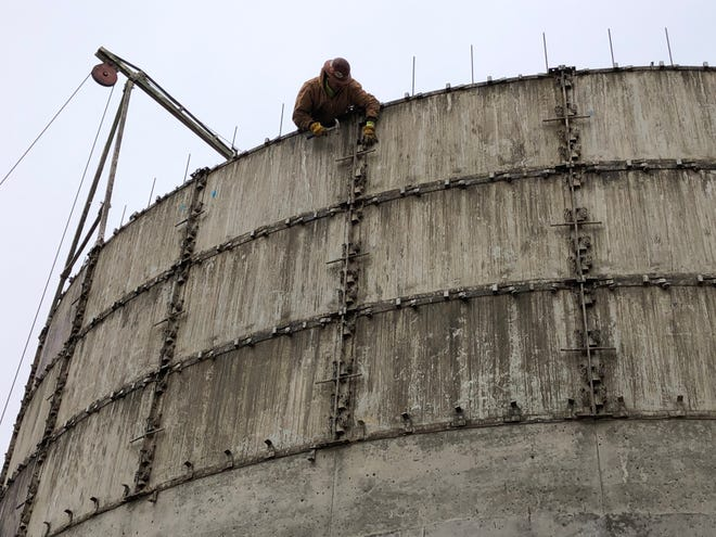 A crewman with McPherson Concrete of McPherson hammers a form into place Thursday morning as part of the new silo construction to expand Midland Marketing's Toulon elevator east of Hays on Old Highway 40.