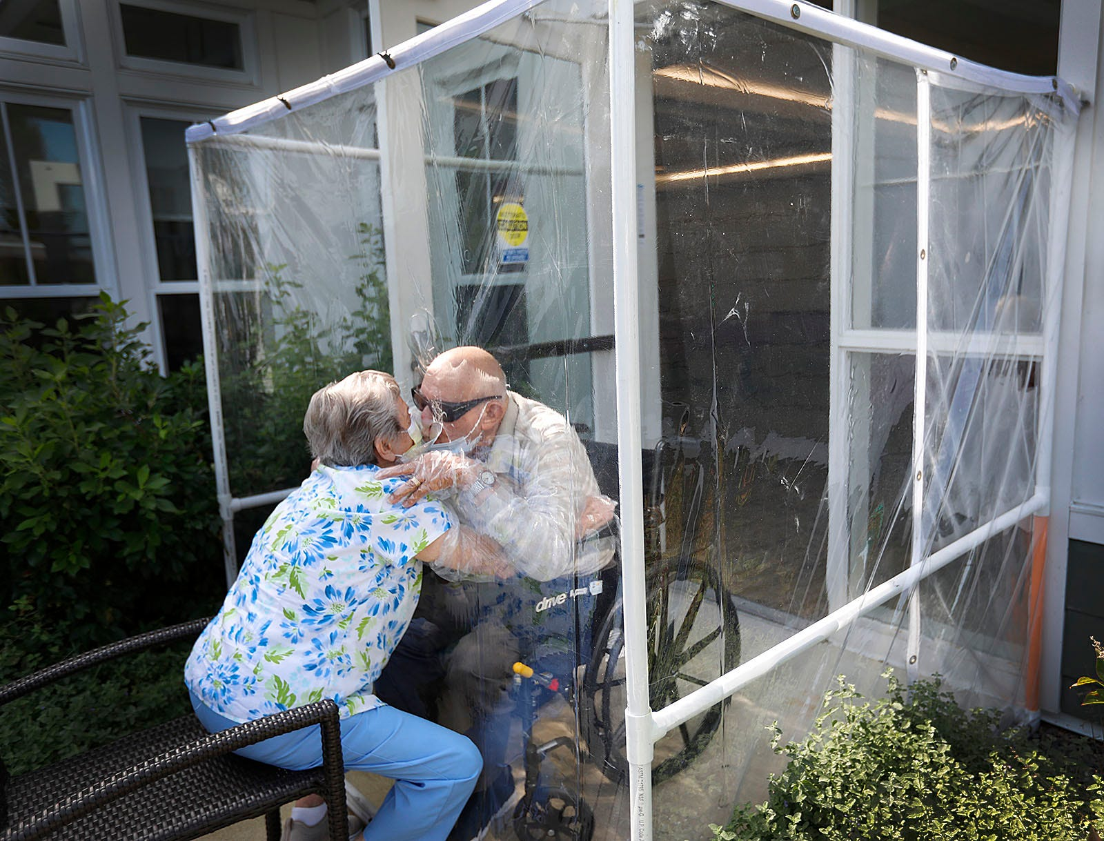 Maryann Salvatore kisses her husband Mario through protective plastic at the Dwyer Home in South Weymouth on Thursday, Sept. 24, 2020.
