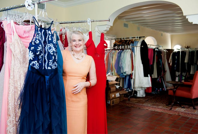 Laura Wissa poses Wednesday with the more than 600 donated prom dresses in her home in Palm Beach.