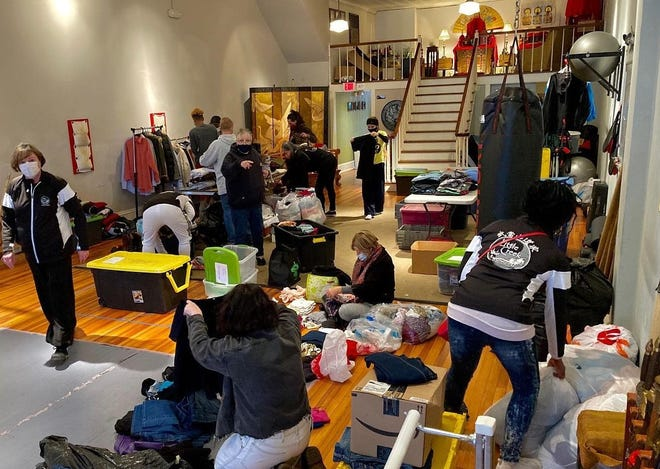 Volunteers sort clothing donated for those in need at Little Creek Kung Fu on North Sycamore Street in Petersburg which has been turned into a storage, sorting, and staging facility for community service programs.