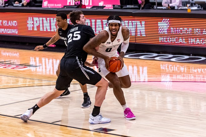 PC's Nate Watson is defended by Xavier's Jason Carter on Wednesday night at Alumni Hall. The Friars won, 83-68.