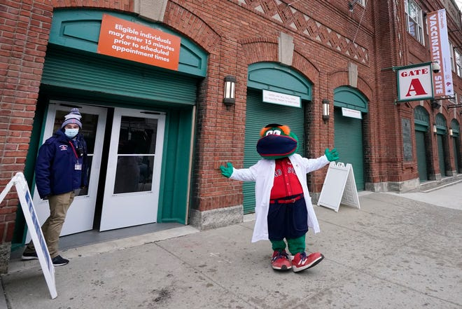 Boston Red Sox mascot, Wally the Green Monster, gestures while dressed in a medical white coat outside Fenway Park, Monday Feb. 1, 2021, in Boston. Fenway Park, which has been serving as one of several large COVID-19 vaccination sites in the Boston area, will be allowed to open up for fans, at limited capacity, beginning in late March according to an announcement from Gov. Charlie Baker on Thursday, Feb. 25, 2021.