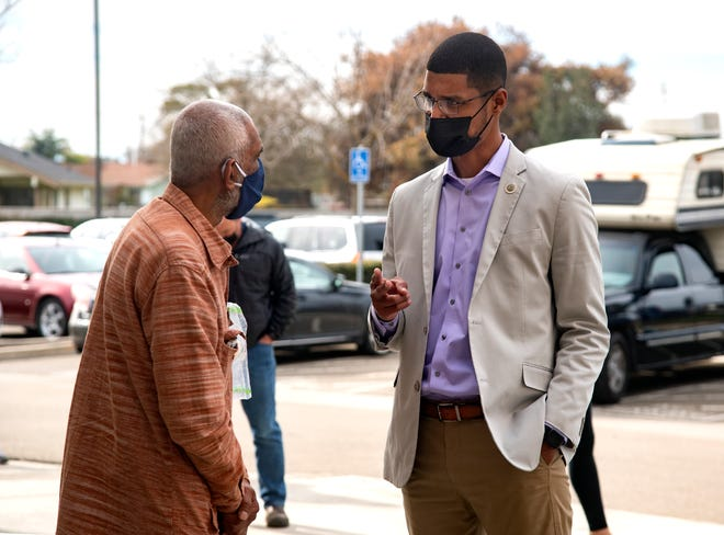 Stockton Mayor Kevin Lincoln, right, talks with Vasu Muda who was waiting in line at a COVID-19 vaccination event at the Progressive Community Church in south Stockton in February.