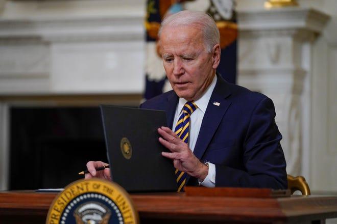 President Joe Biden closes a folder after signing an executive order.