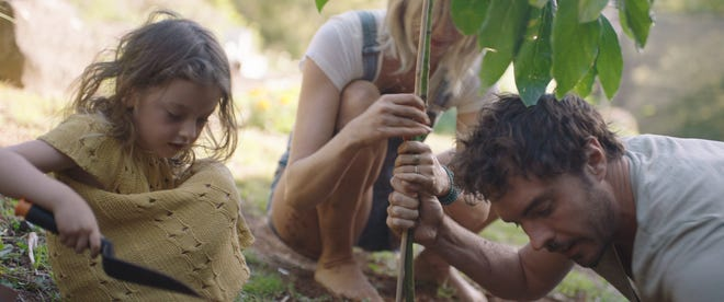 """Writer and director Damon Gameau plants a tree with his wife and daughter in this still from """"2040."""""""