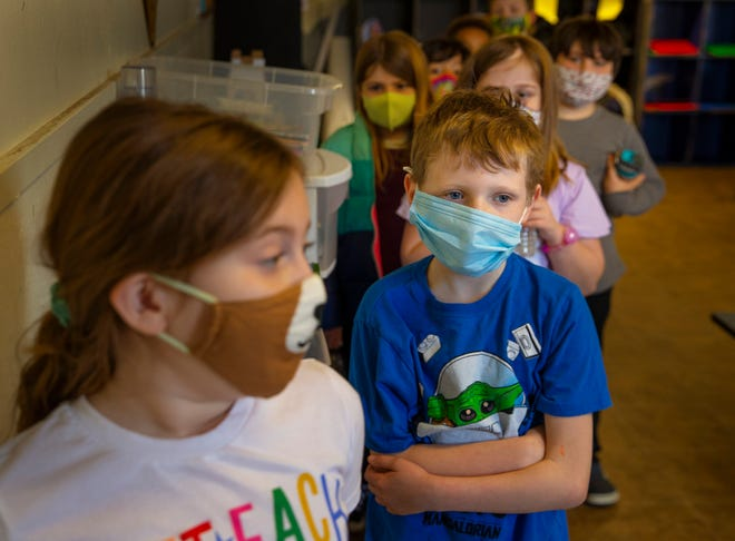 """Masked children, including Naella Cissna, 8, left, and Jonah McKinnon, 7, line up for recess with other children in the Eugene Family YMCA """"Fun Club"""" for school-aged students. The Y program was expanded to accommodate remote learning in conjunction with area schools during the pandemic."""