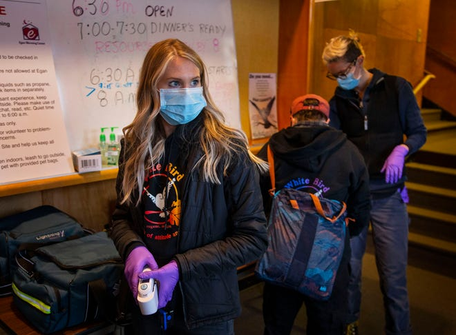Certified Nursing Assistant Celene Eldrich, left, a volunteer for CAHOOTS, waits to screen guests for health concerns at the Egan Warming Center's Springfield, Oregon location in March as the first signs of COVID-19 began to appear in the area.