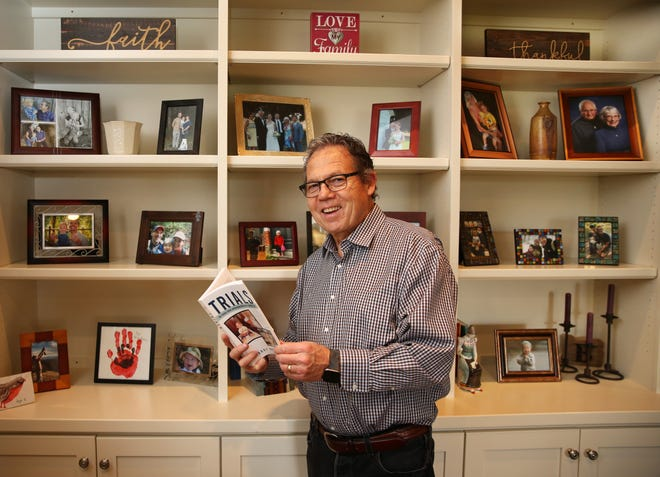 """Larry Bradley with his new book """"Trials: Two Cousins, Cancerand the Doctors Who Fought to Save Their Lives"""" at his family home in Eugene."""