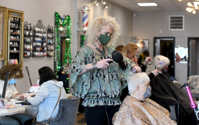 Hair Studio owner Kathy Boyd works with client Jeannette Diszewski, of Jackson Township, on Wednesday morning at the downtown Massillon salon. Boyd remodeled her studio in early 2020 and was forced to close due to the COVID-19 pandemic. She has applied for an economic development grant with the city of Massillon to help pay for a new outdoor sign.