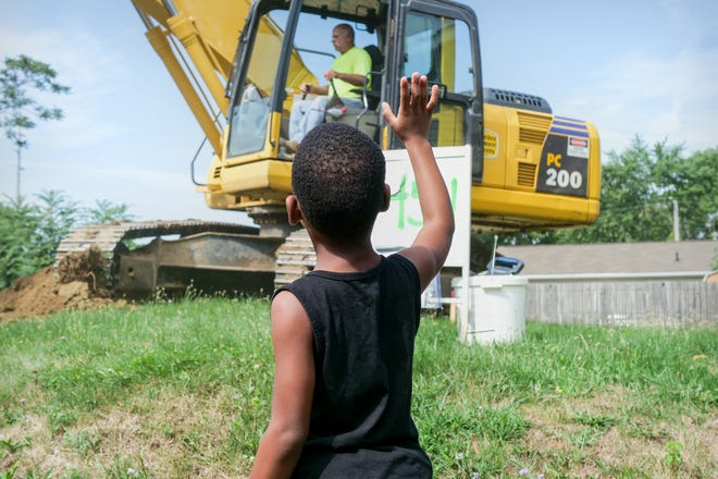 A boy waves to a worker on the southeast Canton Renewal Project in late 2020
