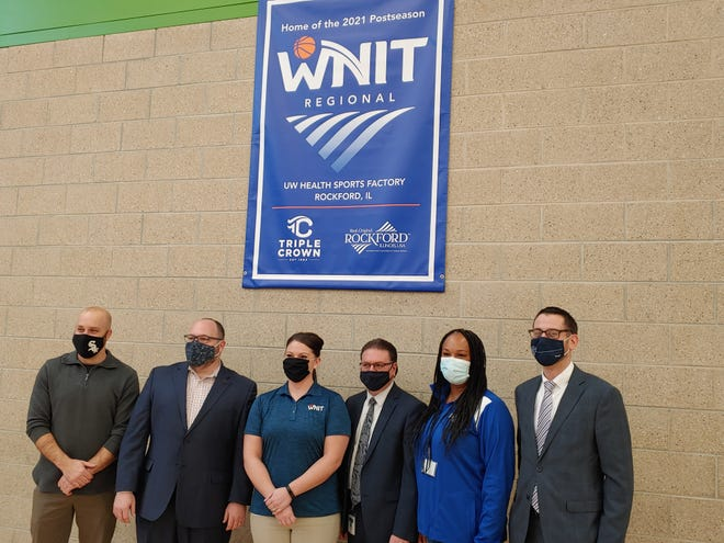 Jay Sandine, from left to right, John Groh, Sarah Molina, Joe Chiarelli, Danielle Potter and Rockford mayor Tom McNamara pose under a WNIT regional banner after Thursday's announcement that an eight-team regional for the tourney will be hosted by the UW Health Sports Factory from March 19-22.