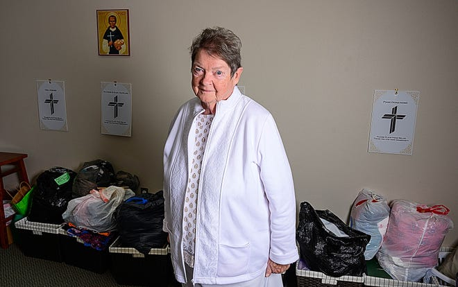Sister Anne Halpin stands in her office in the St. Anastasia Catholic Church, south of St. Augustine, on Wednesday surrounded by bags of clothing she has collected for homeless people.