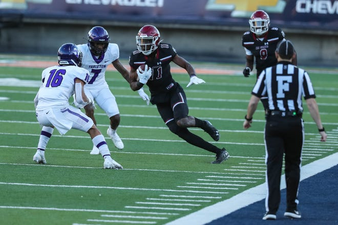 New Mexico State's Andre Bodison (11) runs the ball  while Tarleton's Benjie Franklin (7) and Josh Kemp (16) prepare for the tackle as the Aggies and Texans faced off at the Sun Bowl in El Paso on Sunday.