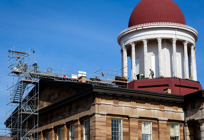 Construction crews work on replacing the deck around the columns of the dome of the Old State Capitol as the renovation project begins in Springfield, Ill., Thursday, February 25, 2021. Workers are using the scaffolding to access the roof area as well as transport materials and debris to the ground. [Justin L. Fowler/The State Journal-Register]