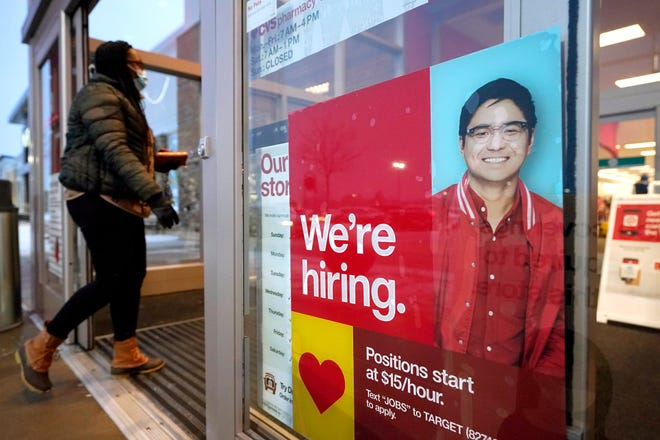 FILE - In this Feb. 9, 2021 file photo, a passer-by walks past an employment hiring sign while entering a Target store location, in Westwood, Mass.   The Federal Reserve says there's evidence that hiring has picked up in recent weeks, though the job market remains badly damaged by the pandemic. In its semi-annual monetary policy report released Friday, Feb. 19, the Fed says job data compiled by payroll processor ADP indicate that employment improved modestly through early February.   (AP Photo/Steven Senne, File)