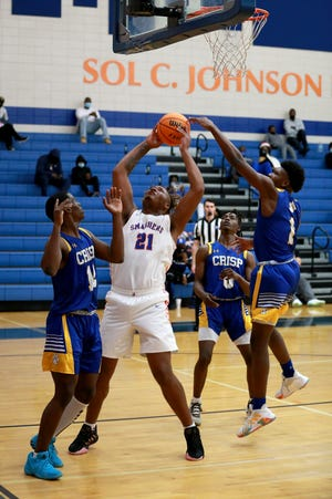 Johnson's Jaheim Robinson works under the basket against a Crisp County double team by Sirad Bryant and Cortez Thomas during Wednesday night's GHSA first-round playoff game at Johnson.