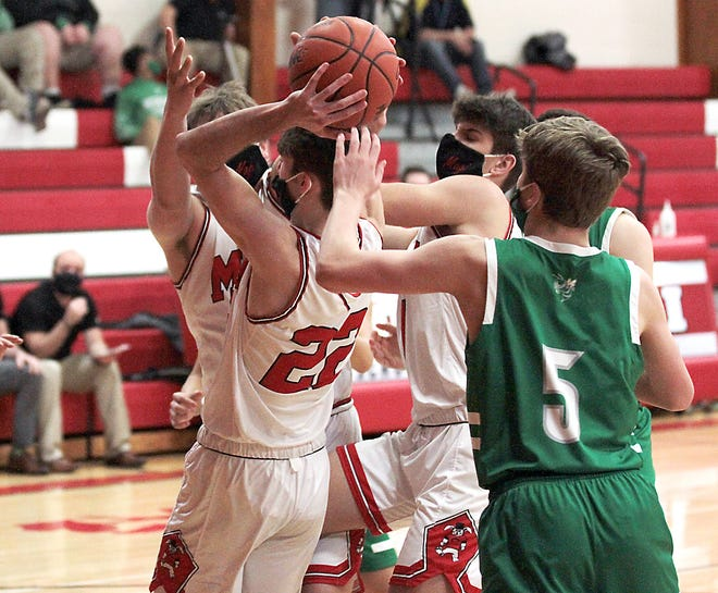 Nate Wagner (22) of Colon rips down a rebound around many other players in Wednesday's game against Mendon.