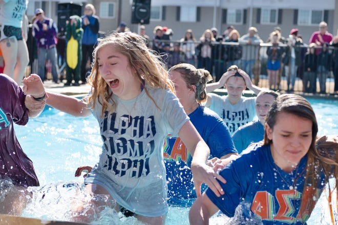 Pittsburg State University students pull themselves out of a pool of cold water after jumping in at last year's Polar Plunge.