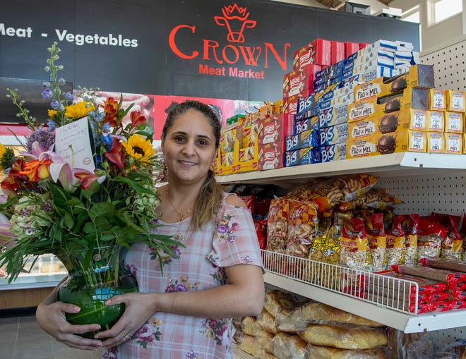 Crown Meat Market owner Graciene Macedo holds flowers she received from JonLundstrom, landlord of the property and former owner of Crown Bakery.