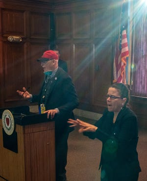 """Sunlight pours through a City Hall window as Dr. Michael P. Hirsh, the city's medical director, speaks during the weekly COVID-19 briefing Thursday. Dr. Hirsh referenced the George Harrison song """"Here Comes The Sun"""" with a hint of optimism during his talk."""
