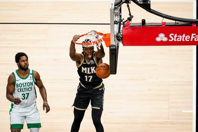 Celtics forward Semi Ojeleye, left, and only watch as  Hawks forward Onyeka Okongwu dunks during the first half Wednesday night in Atlanta.