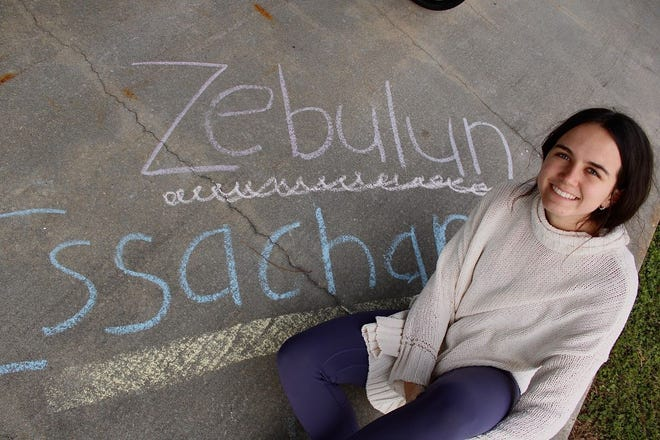 """A student sits beside chalk art bearing the names of the two """"Tribes,"""" student community service organizations at the Baptist College of Florida."""