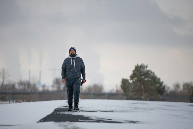 Derrick Fletcher walks around the snow covered track at Pueblo East High School on Thursday morning