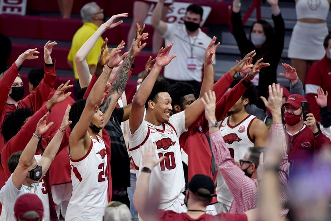Arkansas forward Ethan Henderson (24) and Arkansas forward Jaylin Williams (10) celebrate with teammates and fans after beating Alabama 81-66 during the second half of an NCAA college basketball game in Fayetteville, Ark. Wednesday, Feb. 24, 2021. (AP Photo/Michael Woods)