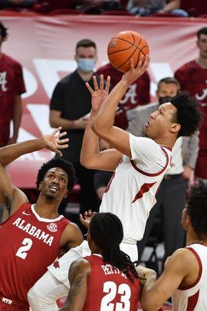 Arkansas forward Jaylin Williams (10) shoots over Alabama defender Alabama forward Jordan Bruner (2) during the first half of an NCAA college basketball game in Fayetteville, Ark. Wednesday, Feb. 24, 2021. (AP Photo/Michael Woods)