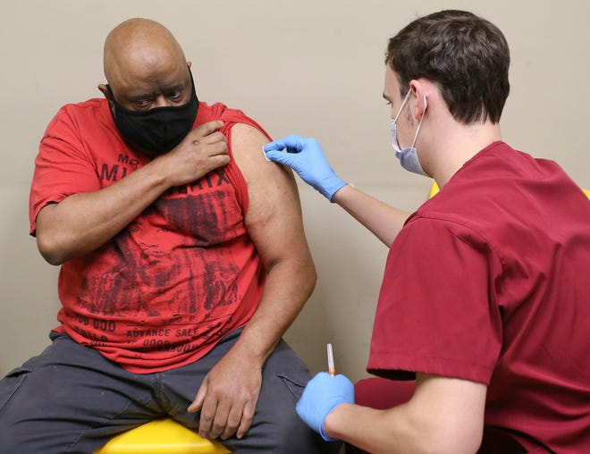 University of Alabama nursing students administered COVID-19 vaccines to patients at the Good Samaritan Clinic in Northport Thursday, Feb. 25, 2021. Nursing student Michael Bottorff prepares to administer the vaccine to James Drew. [Staff Photo/Gary Cosby Jr.]