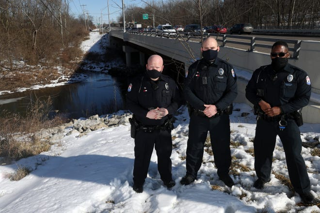 Whitehall Division of Police officers Charles Stonerock (left), Shane McGee and Joseph White stand Feb. 23 near a bridge spanning the Big Walnut Creek between Fairway Boulevard and Noe Bixby Road. It is where the trio rescued a man from the icy water below in January.