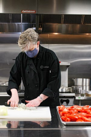 Kate Baker, co-owner and head chef of Belmont's newset restaurant, Trinktisch, prepares food for takout and delivery.