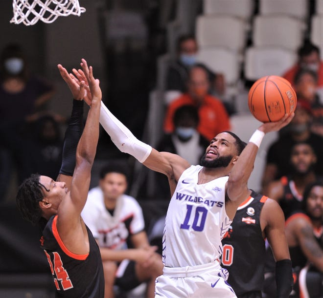 ACU's Reggie Miller (10) shoots over Sam Houston's Donte Powers after coming up with a steal on an inbounds pass beneath the basket. Miller scored and drew a foul on the play. The three-point play gave ACU a 24-21 lead.