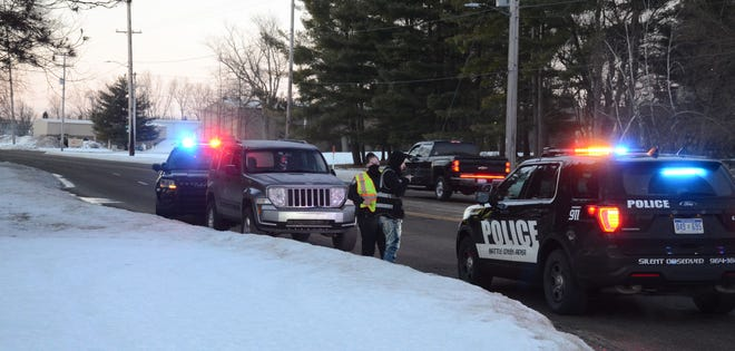 Battle Creek police talk with the driver of an SUV after officers said he struck a pedestrian Thursday morning.
