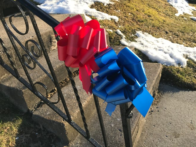 Red and blue ribbons adorn a railing in Audubon, paying tribute to Michael McCausland, a police officer and volunteer firefighter in the borough.